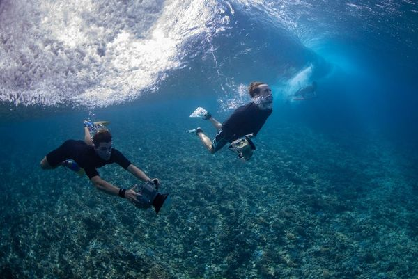 Photographer Ben Thouard and a colleague swimming underwater with cameras in waterproof housings.