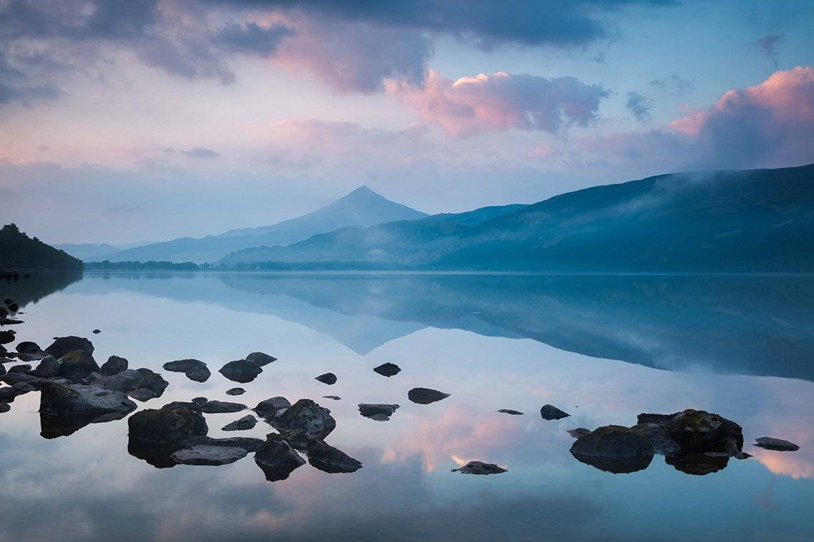 A mountain reflected in a loch at dawn, with an arc of rocks in the foreground.