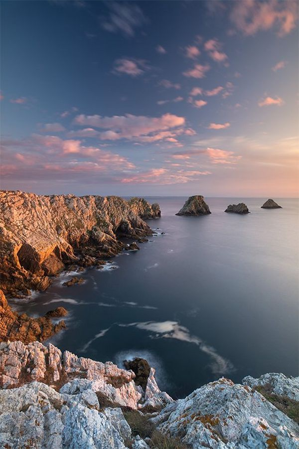 A rocky coastline curving into the distance, ending in three separate rock stacks.