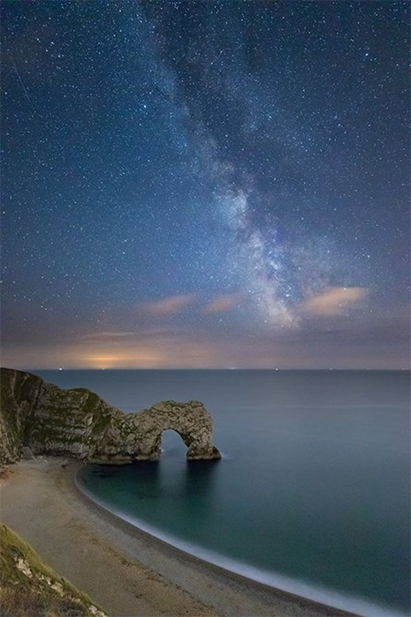 Stars fill the sky in a long-exposure shot looking over the coastline towards a rock arch.