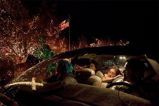 A family of four sit in a car with a creamy-coloured leather-upholstered interior, looking at Christmas lights, some of which are reflected in the windscreen of the car.