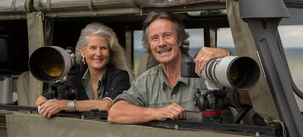 Photographers Jonathan and Angela Scott lean on the side of a camouflaged window, their Canon cameras with telephoto lenses set up in front of them, ready to photograph wildlife.
