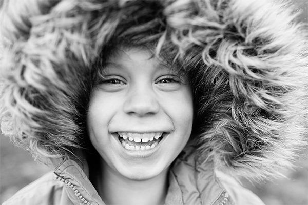 A close-up of a smiling, young boy wearing a hood with fur around the edges.