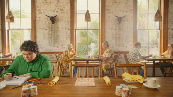 A still from a healthcare advert shot by Alice Gu of a teenage girl in a green shirt sat at a long dining table.