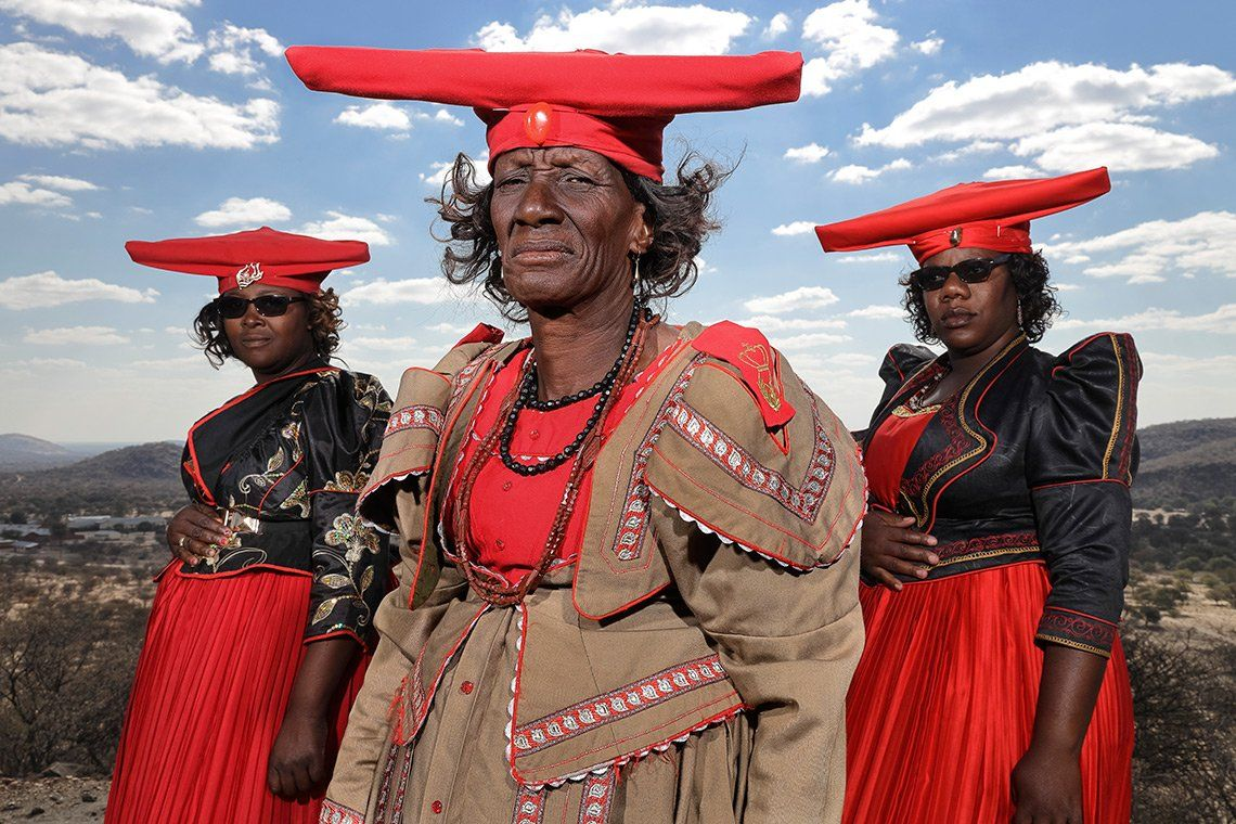 Three Herero women stand in a symmetrical triangular pose, wearing red, khaki and black colonial-style dresses and jackets. They also wear red wide-brimmed hats that lift up at each end like cows' horns.