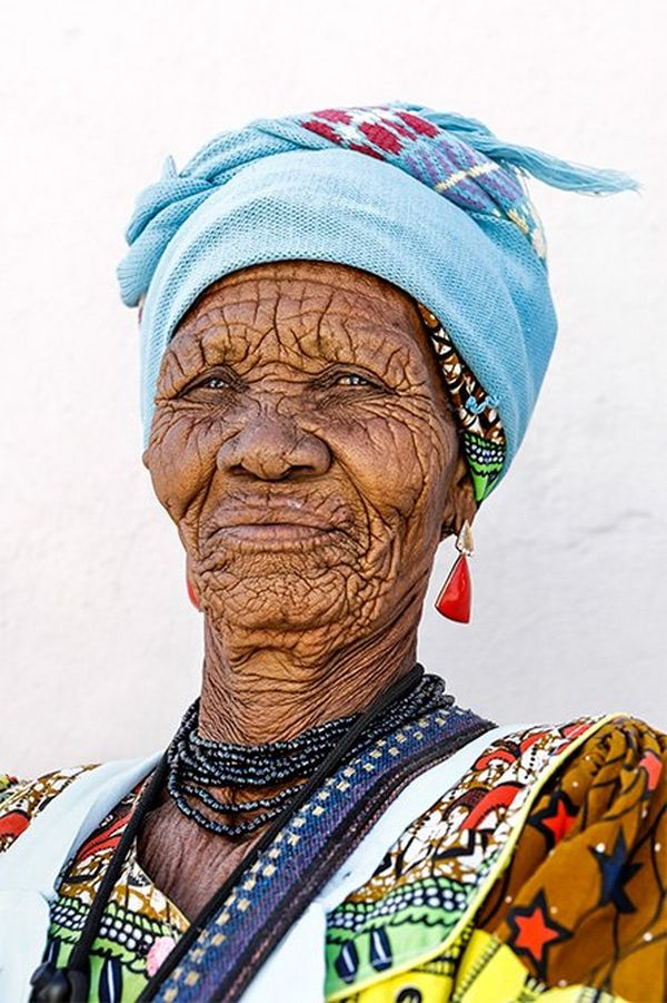 An elderly Namibian woman wearing a colourful patterned dress, dark blue beaded necklace, light blue headscarf, and earrings with large, triangle-shaped red stones.
