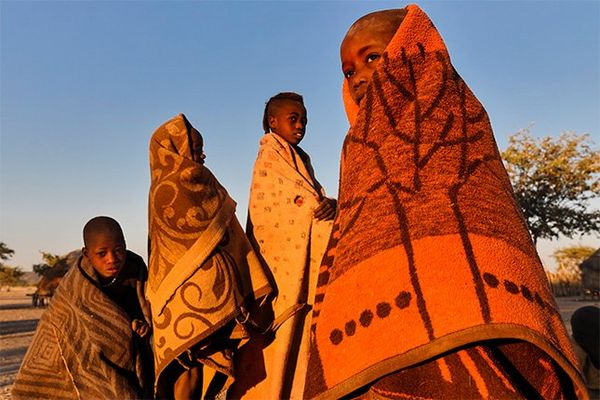 Four Himba boys drape themselves in predominantly ochre and dun coloured wraps with bold patterns.