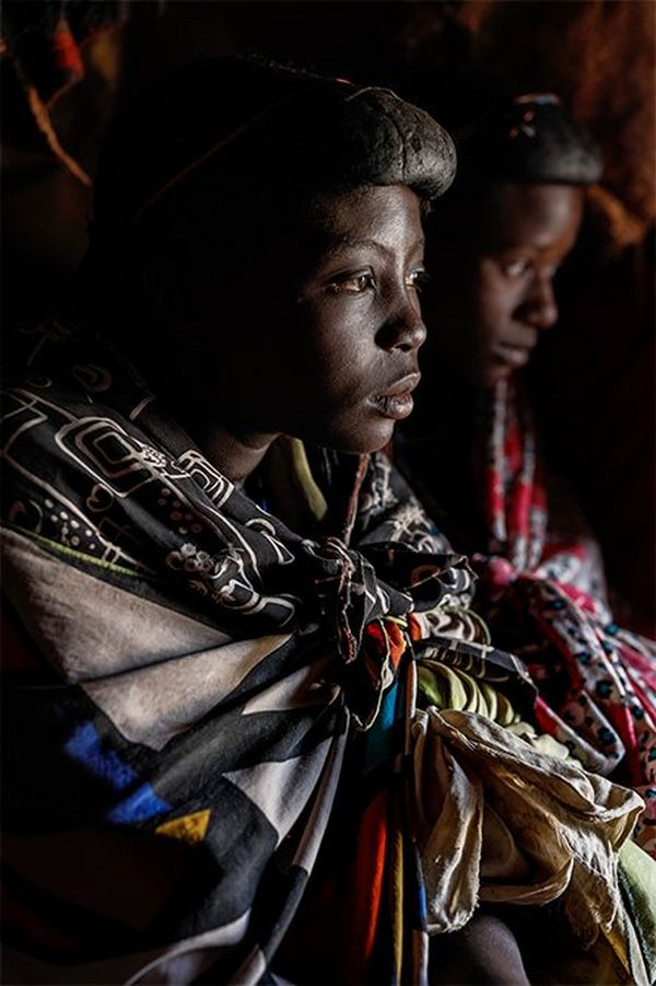 A thoughtful young Himba woman wearing four or five differently-patterned scarves, all knotted at the front, with a companion out-of-focus in the background.