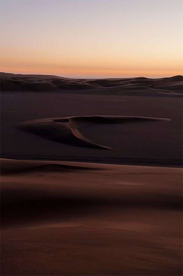 The dunes of the Namibian desert rise to undulating ridges in the distance, with a distinctive dune shaped like a barbed arrowhead in the middle distance.