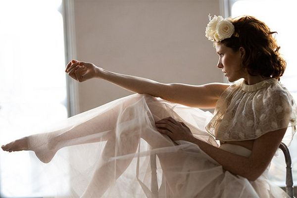 A bride sits in a chair, kicking her legs out. Photo by Félicia Sisco with a Canon RF 85mm F1.2L USM lens.