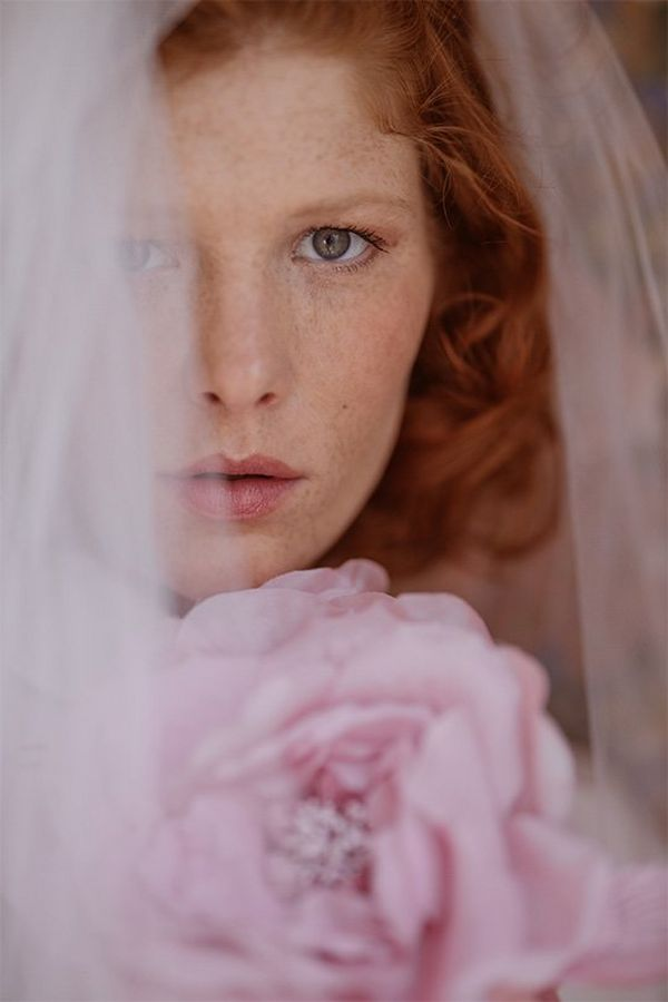 A close-up of a bride wearing a veil and holding pink flowers. Photo by Félicia Sisco with a Canon RF 85mm F1.2L USM lens.