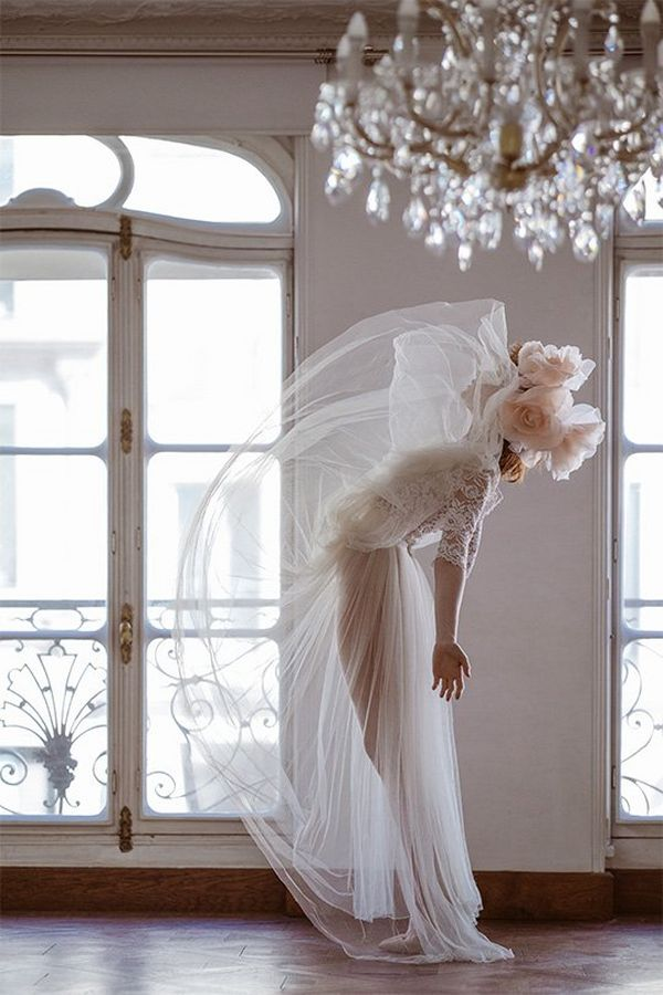 A bride stands in a room and flicks her skirt up above her head. Photo by Félicia Sisco with a Canon RF 85mm F1.2L USM lens.