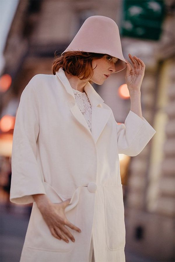 A bride wears a white coat and hat in a city. Photo by Félicia Sisco with a Canon RF 85mm F1.2L USM lens.