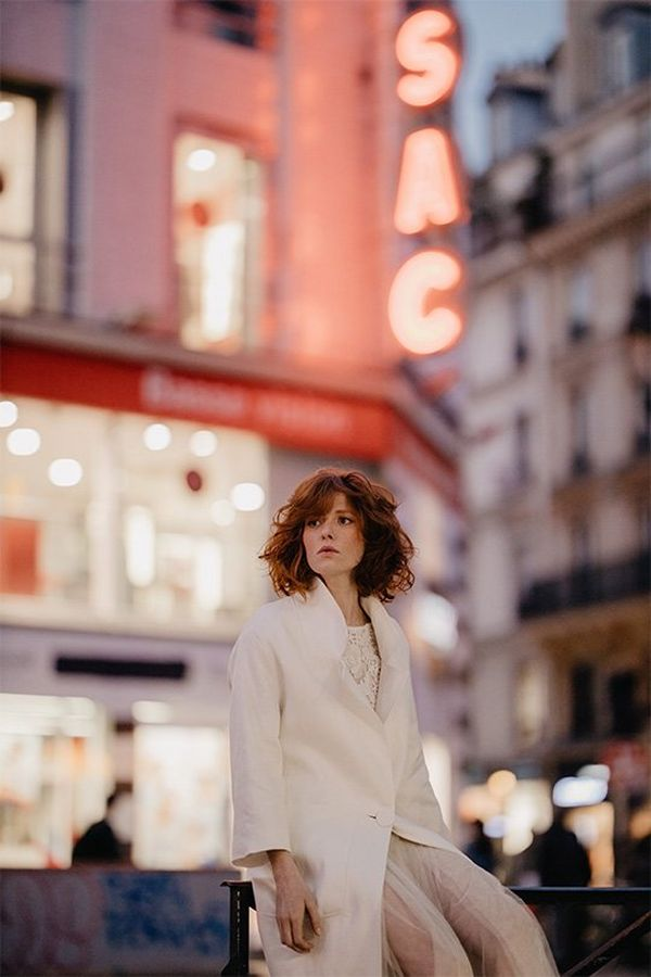 A bride wears a white coat in a city. Photo by Félicia Sisco with a Canon RF 85mm F1.2L USM lens.