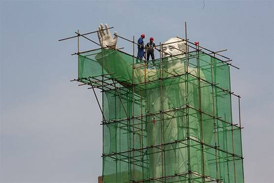 A statue of Mao Zedong covered in scaffolding with two construction workers standing on top.