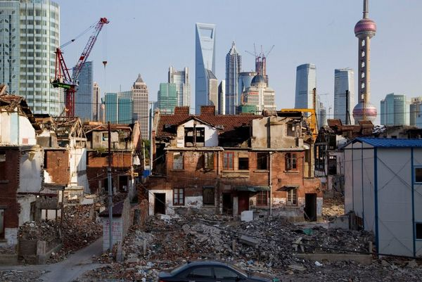 Old buildings being torn down, leaving piles of rubble in the foreground, with cranes and skyscrapers visible in the background.