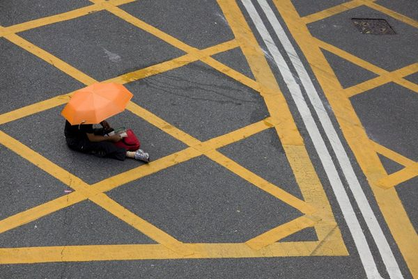 A person with an orange umbrella sitting on the tarmac of a yellow box junction.