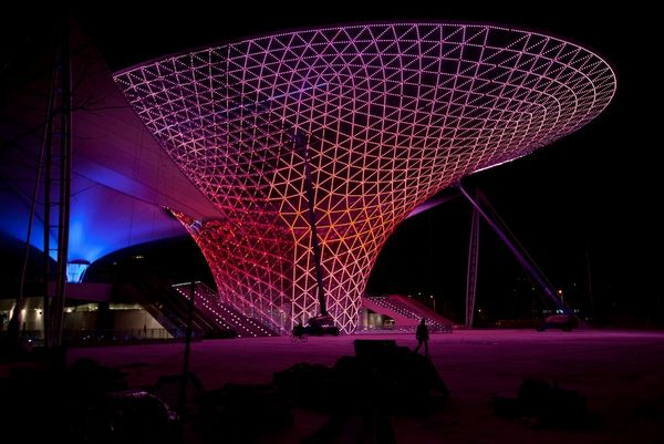 An example of modern architecture in China, Shanghai's Expo Axis lit up with pink light in geometric lines.