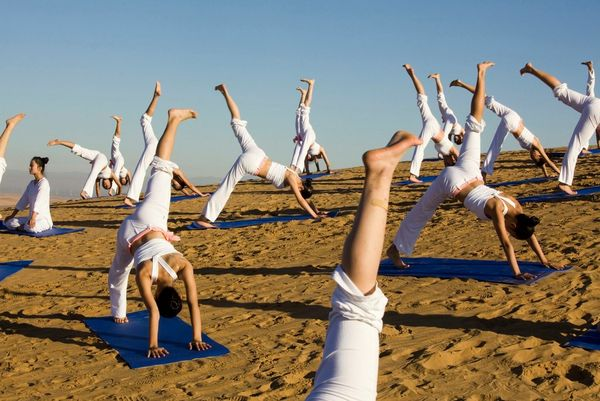 A group of women all wearing white performing yoga on a sand dune in the Kubuqi Desert in China's Inner Mongolia Autonomous Region.