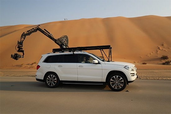 A car in the desert has a Canon EOS C700 FF attached to a crane arm out the back.