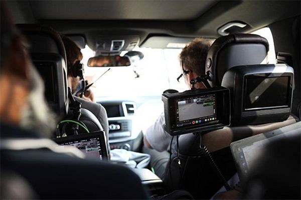 A film crew in the camera car watch footage on monitors.