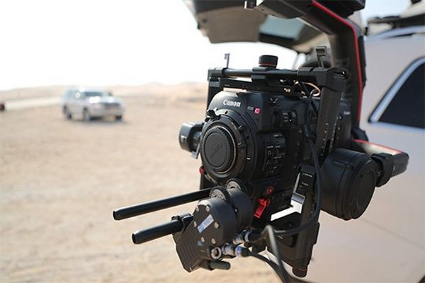 A close-up of the Canon EOS C700 FF mounted on the end of a crane arm attached to a film car.