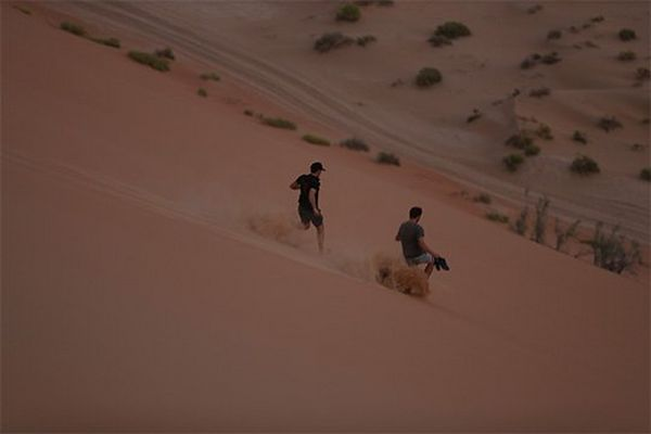 Cameramen run down the side of a high, steep sand dune.