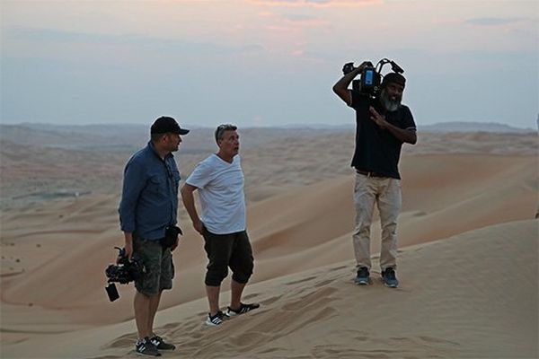 Three men in a desert, two holding Canon video cameras ready to film.