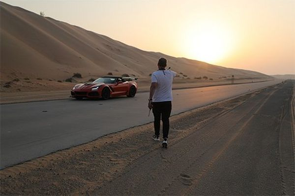 DOP Brett Danton walks towards the orange supercar in the desert at sunset.