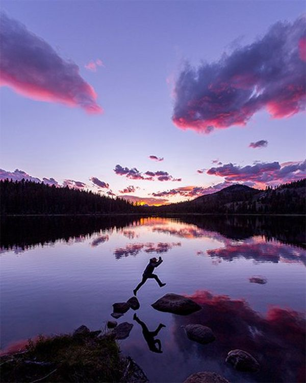 A man leaps between two stepping stones in front of a lake, the sky purple with the setting sun.