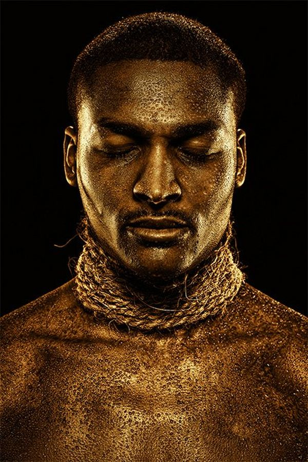 A man with gold-painted skin wears strings of rope around his neck.