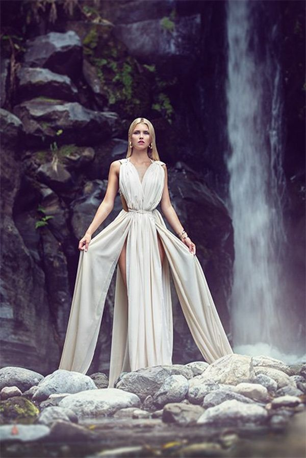 A woman wears a white dress in front of a waterfall.