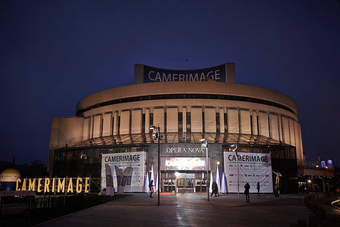 The round, concrete Opera Nova building is seen with a red carpet leading up to its doors, with signs saying 'CAMERIMAGE'.