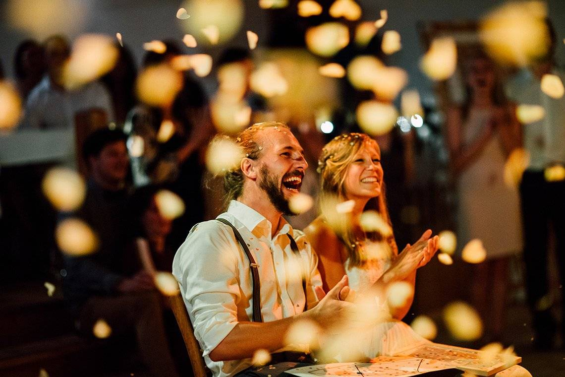 A couple laughing in delight as confetti falls around them. They are in sharp focus, everything else is blurred. Photo by Markus Morawetz.