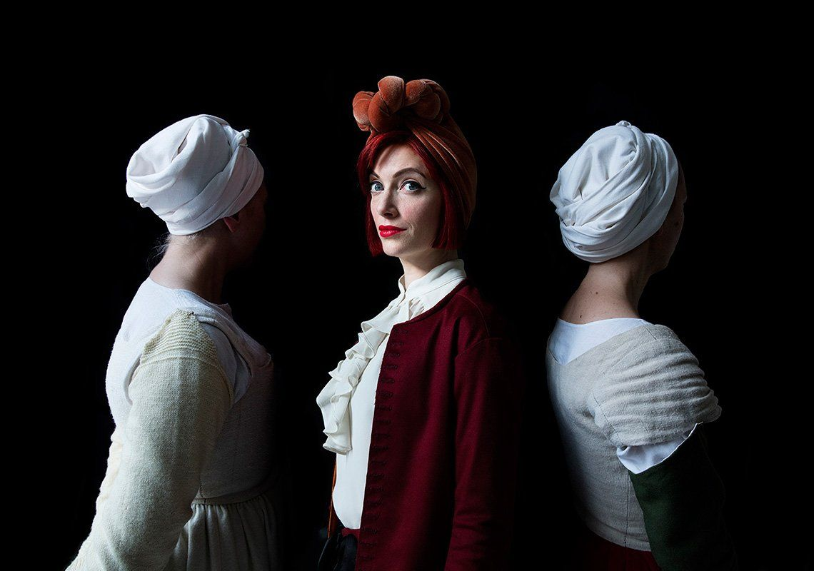 A woman with red hair stands side-on, facing the camera. On either side of her are women facing the other way, wearing old-fashioned white servant-style hats and dresses. They're against a black background.