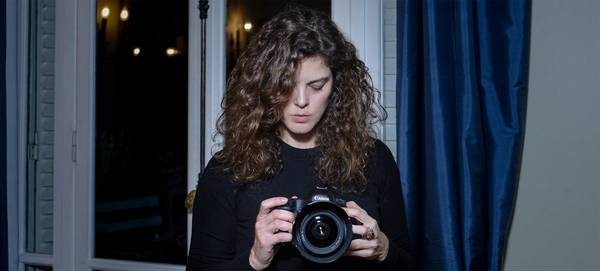 Photographer Carolina Arantes looks down at a Canon camera in her hands.