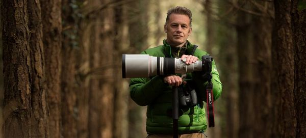 Chris Packham stands in a woodland wearing a green jacket, his hands resting on his Canon 5DS R fitted with a Canon telephoto lens, on a stand.