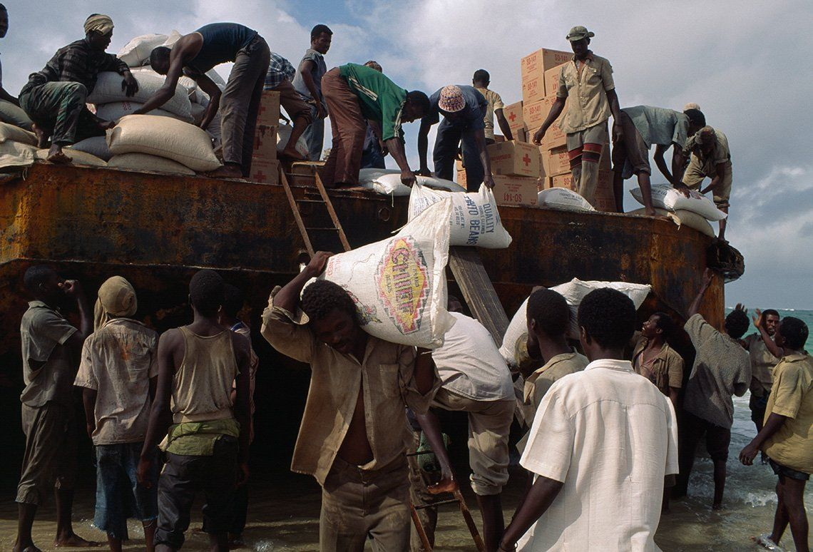 Men unload large sacks from the top of a bus.