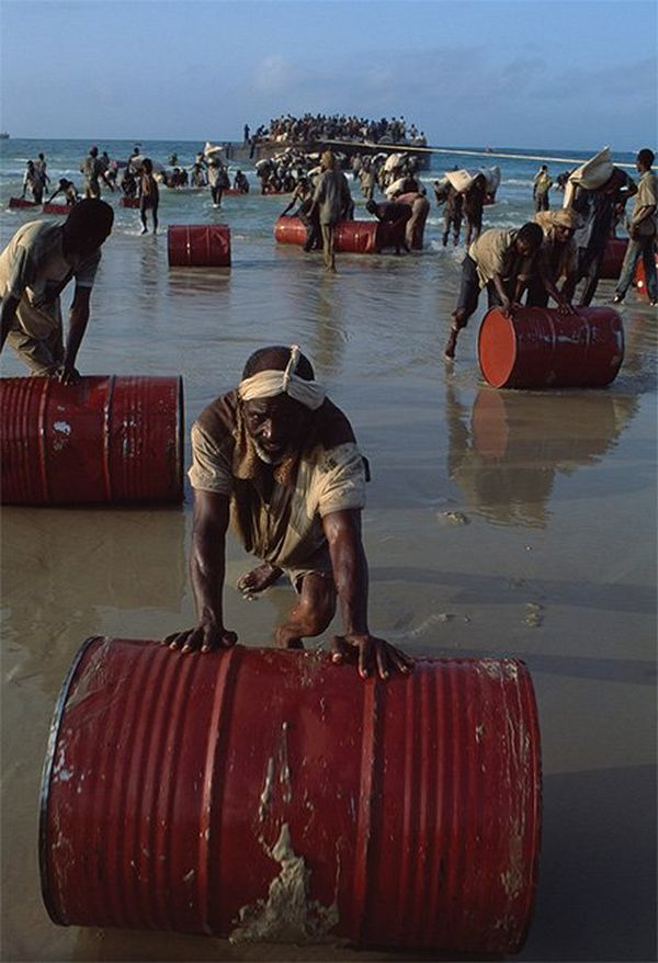 Men roll red barrels out of the sea onto the beach.