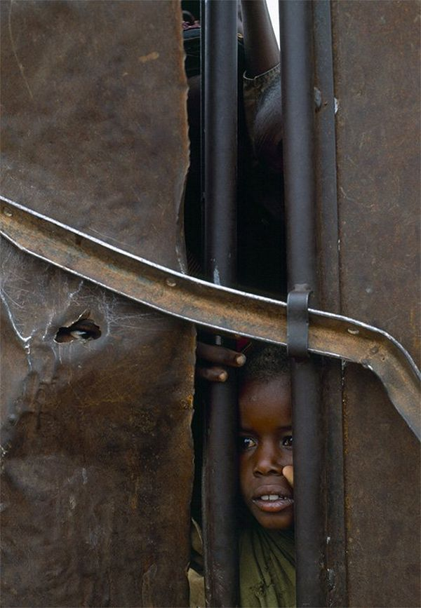 A small child looks through a gap between iron gates.