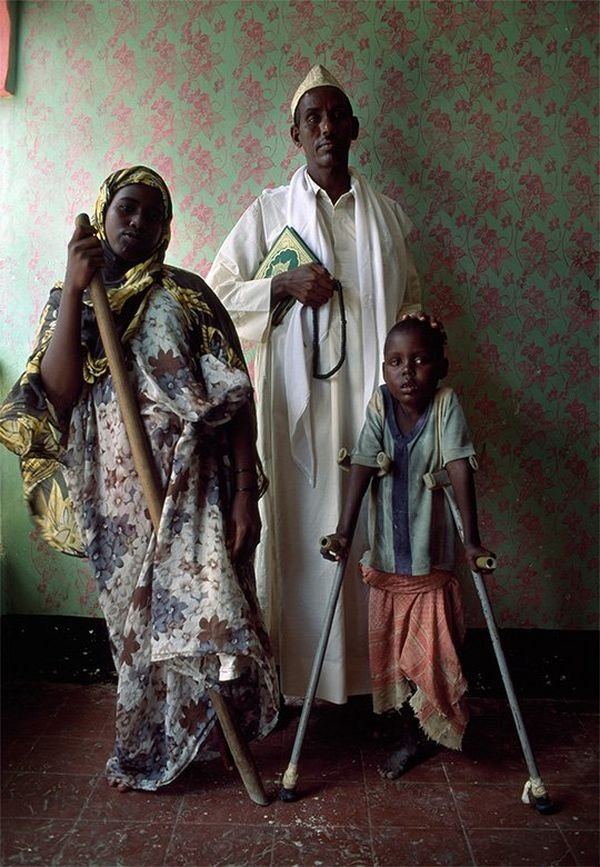 A man, woman and child stand in a room with patterned wallpaper. The child is supported with crutches and the woman with a staff.