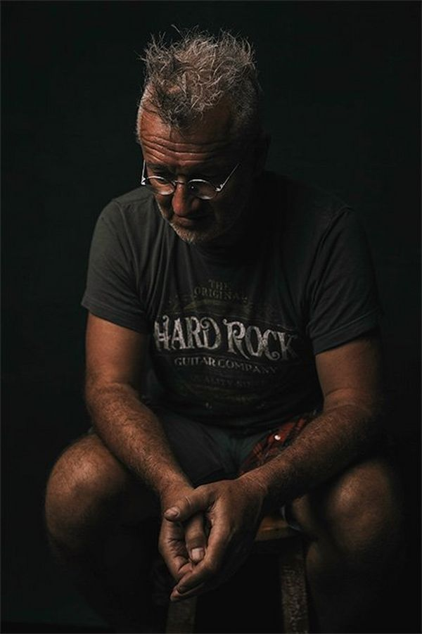 A man with greying hair and steel-rimmed glasses sits with elbows on his knees looking pensively downwards.