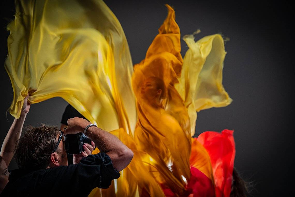 Clive Booth photographs a dancer shrouded in orange and yellow silks.