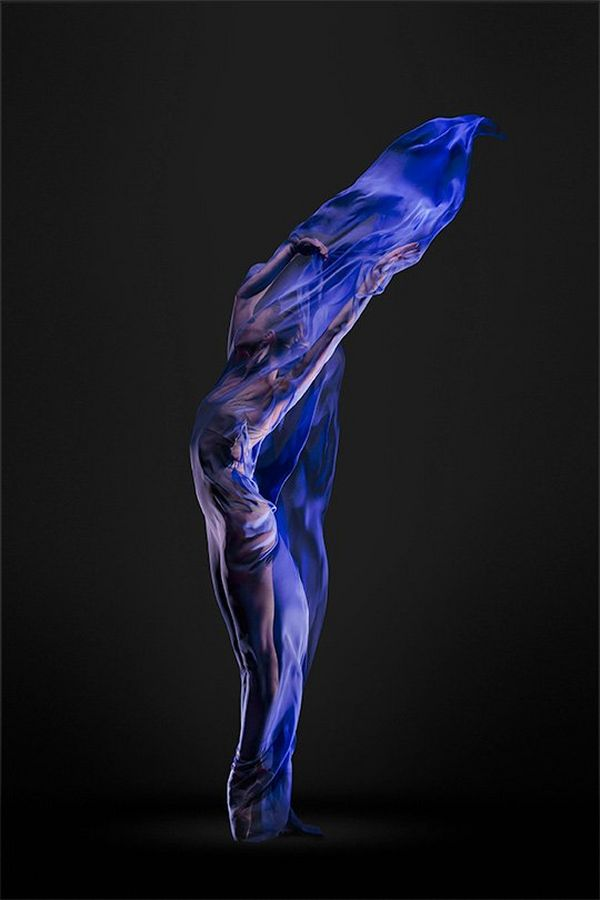 A ballet dancer completely shrouded in blue silks forms a sinuous S-shape like a living flame.