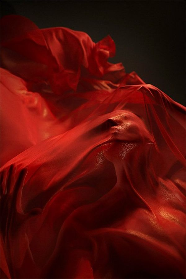 A ballet dancer shrouded in fluttering red silks, photographed from below.