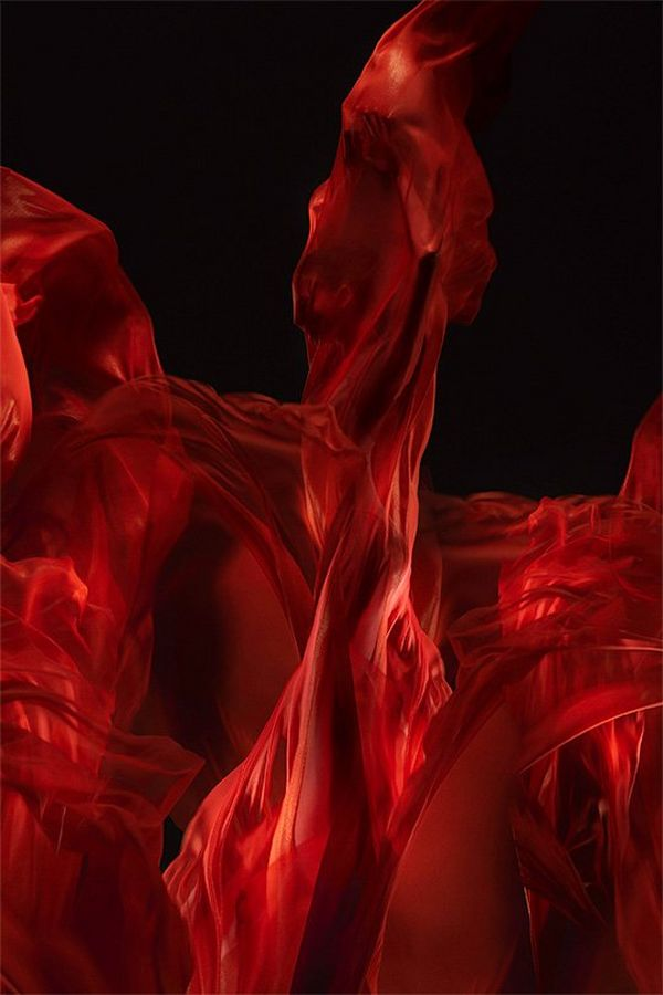 A ballet dancer shrouded in billowing red silks with the appearance of dancing flames.
