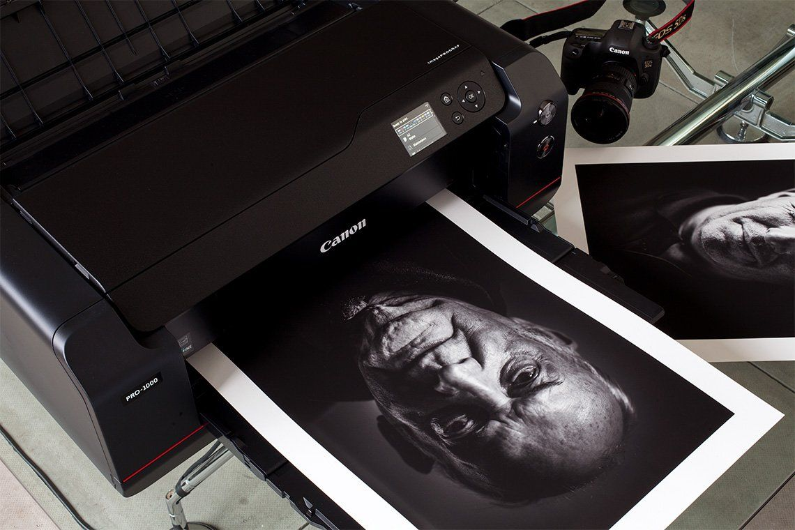 A printer printing out a black and white portrait of an older man.