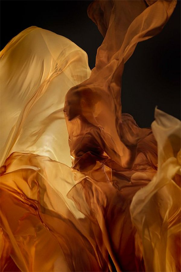 A ballet dancer's profile covered by yellow silk fabric that is billowing around her like a flame.