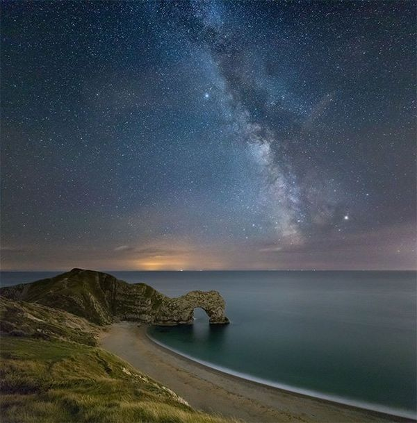The Milky Way over a coastal arch.