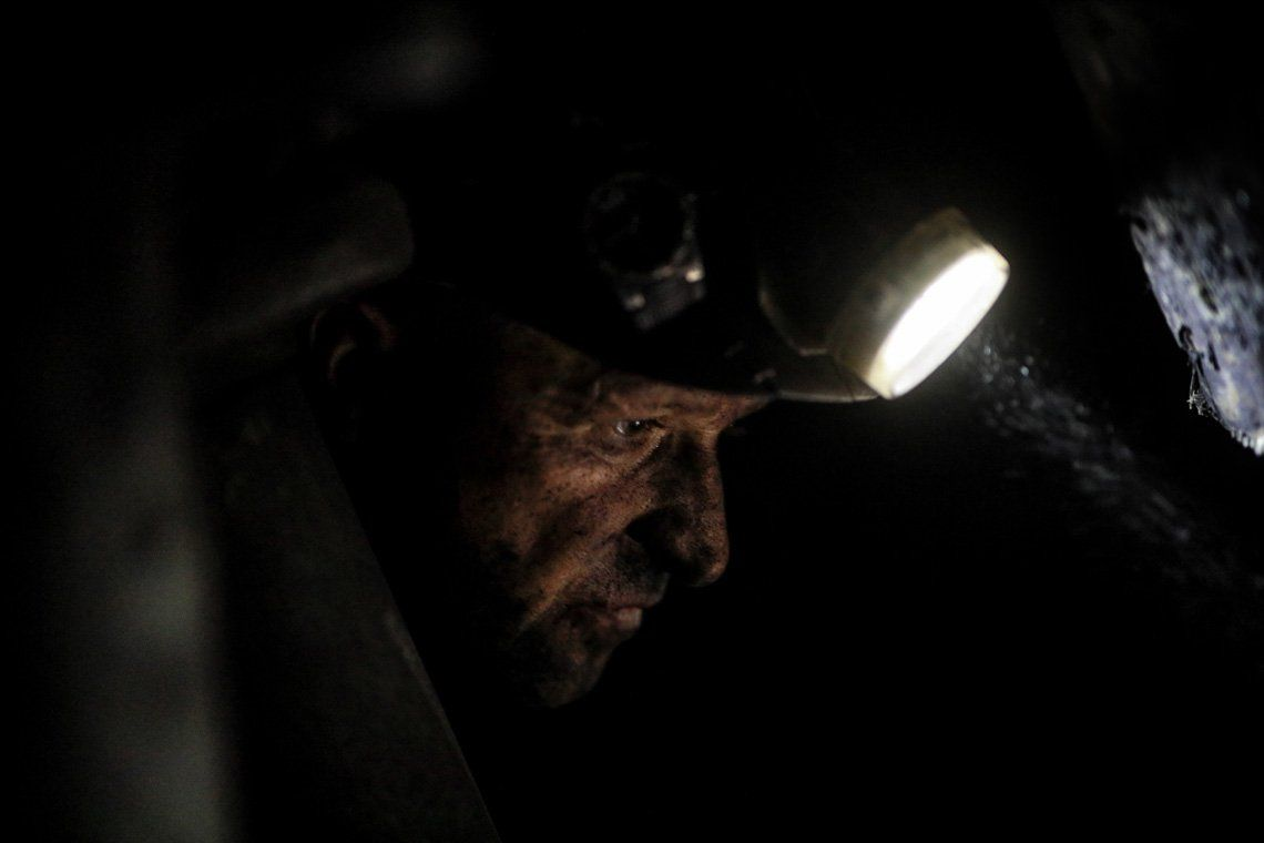 A close-up of a miner's face looking down, lit by his headlamp